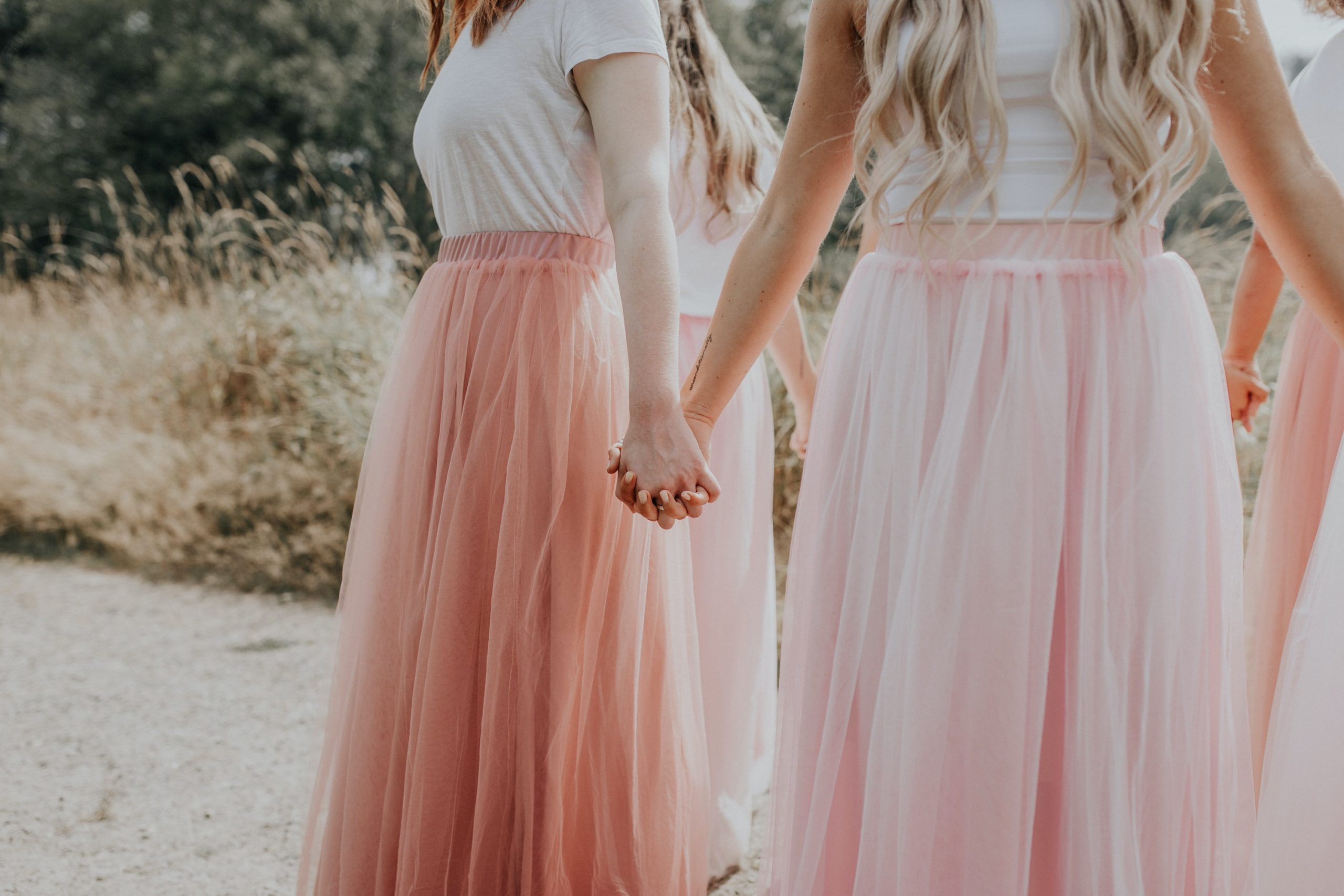 Women holding hands in pink